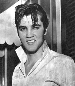 Photo is of Elvis at age 23, in 1958. He is in a white shirt with the collar popped up, and his hair is in front of his face.